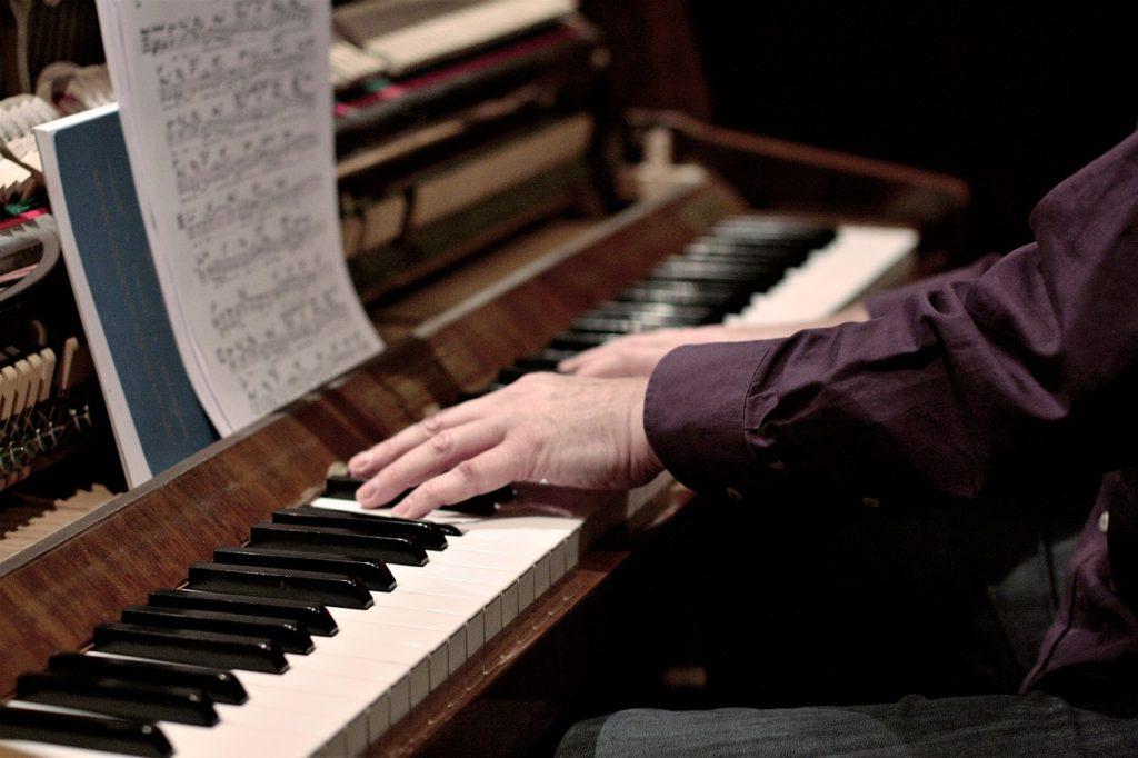 Une personne appliquant parfaitement la forme à 5 doigts sur un piano